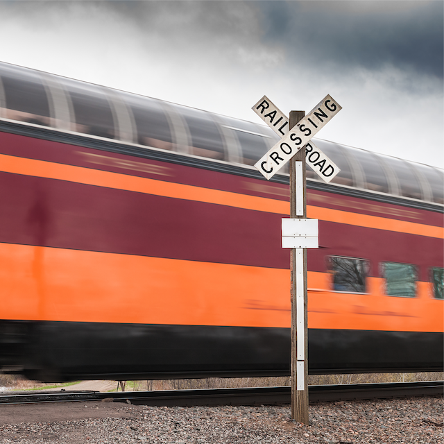 Moving train passing by rail crossing sign